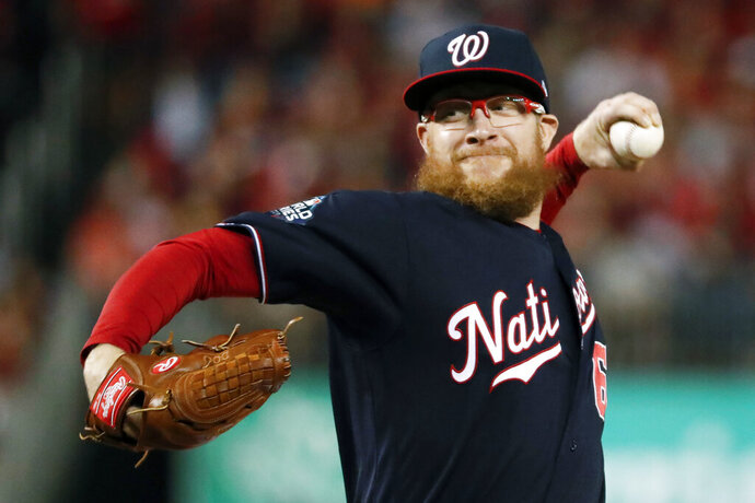 FILE - In this Oct. 27, 2019, file photo, Washington Nationals relief pitcher Sean Doolittle throws during the seventh inning of Game 5 of the baseball World Series against the Houston Astros, in Washington. The Nationals told their minor leaguers on Monday, June 1, 2020, they will receive their full weekly stipends of $400 at least through June after Washington reliever Sean Doolittle tweeted that the team's major league players would cover a planned cut in those payments.(AP Photo/Jeff Roberson, File)