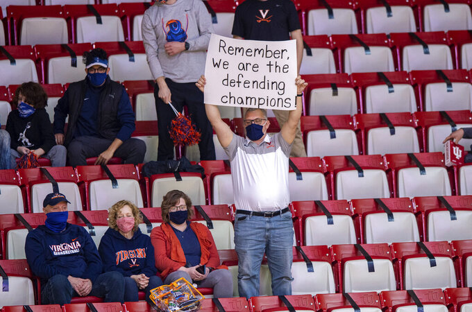 A Virginia fan holds up a sign before the start of a first-round game against Ohio in the NCAA men's college basketball tournament, Saturday, March 20, 2021, at Assembly Hall in Bloomington, Ind. (AP Photo/Doug McSchooler)