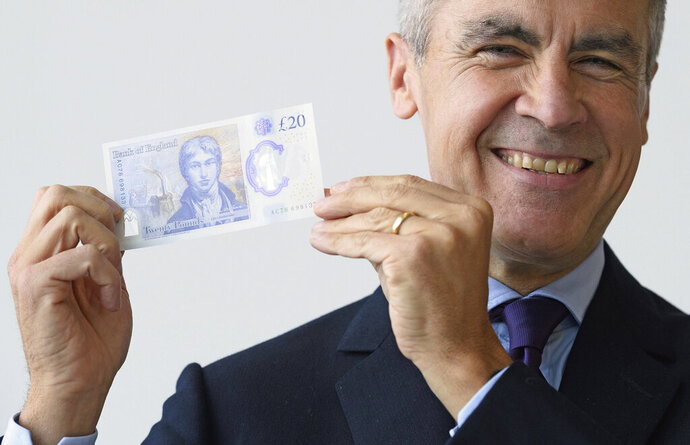 Governor of the Bank of England, Mark Carney, poses with a sample of the new 20 pound bank note, featuring a portrait of the English artist JMW Turner, at the Turner Gallery in London, Thursday Oct. 10, 2019. The new polymer note, which contains sophisticated security features, will be issued into general circulation early 2020.(Leon Neal/PA via AP)