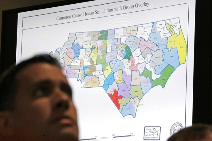 FILE - In this Monday, July 15, 2019 file photo, a state districts map is shown as a three-judge panel of the Wake County Superior Court presides over the trial of Common Cause, et al. v. Lewis, et al, in Raleigh, N.C.  North Carolina has often been cited as an example of political gerrymandering. Now court rulings against its legislative and congressional districts also could become an example for other states. (AP Photo/Gerry Broome, File)