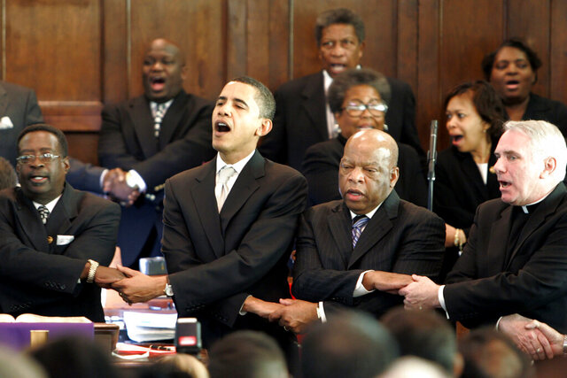 FILE - In this Sunday March 4, 2007, file photo, from left, Brown Chapel AME Church Pastor James Jackson, Democratic presidential candidate Sen. Barack Obama, D-Ill., U.S. Rep. John Lewis, D-Georgia, and Rev. Clete Kiley, hold hands and sing at the end of a church service in Selma, Ala., on the commemoration of the Rev. Martin Luther King Jr. protest march from Selma to Montgomery, Ala. Lewis, who carried the struggle against racial discrimination from Southern battlegrounds of the 1960s to the halls of Congress, died Friday, July 17, 2020. (AP Photo/Rob Carr, File)