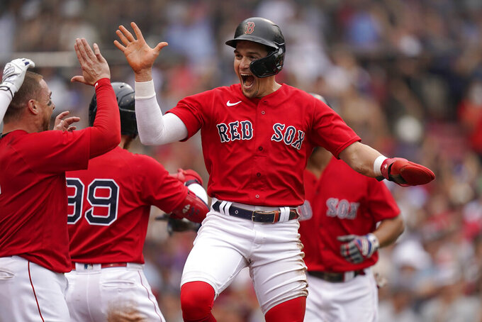 Boston Red Sox's Enrique Hernandez, center, celebrates with teammates after scoring on a sacrifice fly by Xander Bogaerts in the eighth inning of a baseball game against the New York Yankees, Sunday, July 25, 2021, in Boston. (AP Photo/Steven Senne)
