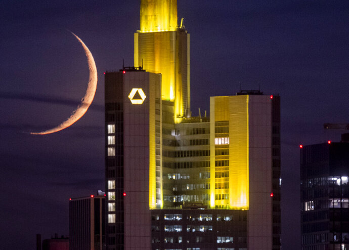 The crescent moon sets behind the Commerzbank building in Frankfurt, Germany, late Saturday, Sept. 19, 2020. (AP Photo/Michael Probst)
