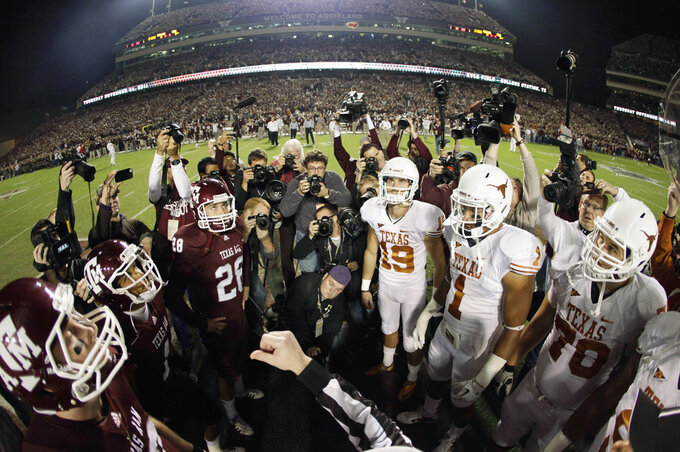 CORRECTS DATE OF PHOTO TO NOV. 24, 2011 - FILE - In this Nov. 24, 2011, file photo, an official tosses the coin in the air before the start of an NCAA college football game between Texas and Texas A&M in College Station, Texas. Texas state Rep. Lyle Larson on Tuesday, Nov. 27, 2018, filed a bill that would require his alma mater Texas A&M and Texas to resume their storied football rivalry during the Thanksgiving holiday period. The proposal would require an annual nonconference game on the fourth Thursday, Friday or Saturday of November. The teams last met Thanksgiving Day 2011 in College Station. (AP Photo/David J. Phillip, File)