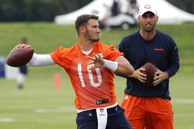 FILE - In this July 26, 2019, file photo, Chicago Bears quarterback Mitchell Trubisky, left, throws a ball as quarterbacks coach Dave Ragone looks on during an NFL football training camp in Bourbonnais, Ill. The Chicago Bears heard plenty of talk about their possible regression during an offseason brought on by Cody Parkey's double-doink field goal miss. Their solution for backsliding following a 12-4 season is how much they believe in quarterback Mitchell Trubisky's development. (AP Photo/Nam Y. Huh, File)