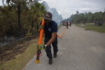 Broward Sheriff Fire Rescue firefighters Rubens Cela moves a hose into position as his team extinguish spot fires, May 14, 2020, off Everglades Boulevard South in Golden Gate Estates, Fla. (Jon Austria/Naples Daily News via AP)