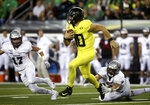 Oregon's Justin Herbert, center, runs the ball against Montana's Robby Hauck, left, and Cole Grossman, right, during the second quarter of an NCAA college football game Saturday, Sept. 14, 2019, in Eugene, Ore. (AP Photo/Chris Pietsch)