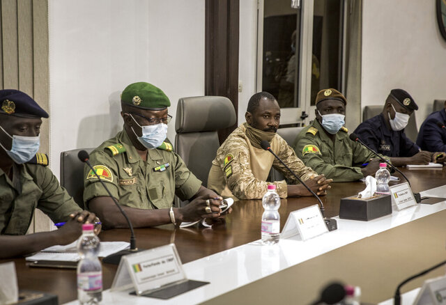 Col. Assimi Goita, center, who has declared himself the leader of the National Committee for the Salvation of the People, is accompanied by group spokesman Ismael Wague, left, and group member Malick Diaw, center-left, as they meet with a high-level delegation from the West African regional bloc known as ECOWAS, at the Ministry of Defense in Bamako, Mali, Saturday, Aug. 22, 2020. Top West African officials are arriving in Mali's capital following a coup in the nation this week to meet with the junta leaders and the deposed president in efforts to negotiate a return to civilian rule. (AP Photo)