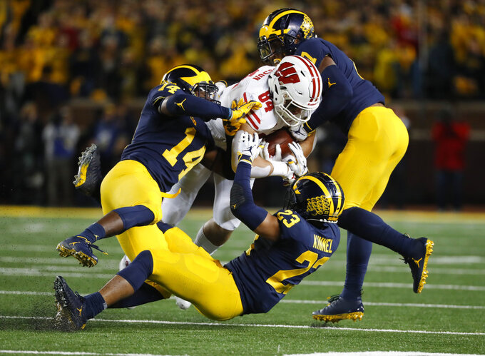 Michigan defensive backs Josh Metellus (14), Tyree Kinnel (23) and linebacker Khaleke Hudson (7) gang-tackle Wisconsin tight end Jake Ferguson (84) after a catch during the first half of an NCAA college football game in Ann Arbor, Mich., Saturday, Oct. 13, 2018. (AP Photo/Paul Sancya)