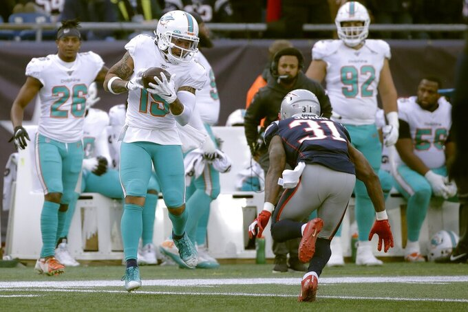 Miami Dolphins wide receiver Albert Wilson, left, catches a pass in front of New England Patriots defensive back Jonathan Jones in the second half of an NFL football game, Sunday, Dec. 29, 2019, in Foxborough, Mass. (AP Photo/Elise Amendola)