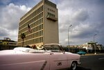 Tourists take a joy ride in a vintage convertible car as they pass the U.S. embassy in Havana, Cuba, Monday, March 18, 2019. The U.S. State Department said Friday, March 15, 2019 that it is eliminating a coveted five-year tourist visa for Cubans, dealing a heavy blow to entrepreneurs and Cuban members of divided families, who used the visas to see relatives in the U.S. and buy precious supplies for their businesses on the island. (AP Photo/Ramon Espinosa)