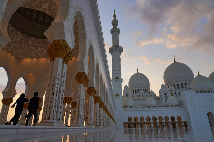 """Tourists walk through Sheikh Zayed Grand Mosque at dusk in Abu Dhabi, United Arab Emirates, Wednesday, Dec. 9, 2020. Abu Dhabi announced Wednesday it would resume """"all economic, tourism, cultural and entertainment activities in the emirate within two weeks."""" It attributed the decision to """"successes"""" in halting the spread of the coronavirus. (AP Photo/Jon Gambrell)"""