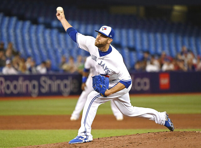 FILE - In this June 28, 2019, file photo, Toronto Blue Jays' David Phelps pitches against the Kansas City Royals during the sixth inning of a baseball game in Toronto. Free agent Phelps and the Milwaukee Brewers finalized a one-year contract on Thursday, Jan. 30, 2020, that guarantees $1.5 million and includes a club option for 2021. (Jon Blacker/The Canadian Press via AP, File)