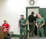 Detention Deputies stand at the doorway as Michael W. Jones Jr., left, sits on a bench in handcuffs and chains while waiting for his initial appearance at the Marion County Jail courtroom, Thursday, Sept. 19, 2019, in Ocala, Fla. Jones, suspected of killing his wife and four children and driving their bodies into Georgia, returned to Florida to face murder charges. (Doug Engle/Star-Banner via AP)