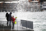 A group of women look on as a wind-driven wave crashes near high tide into the seawall where they stand Tuesday, Jan. 7, 2020, in Seattle. Elevated daytime temperatures and rain in some parts of the Puget Sound region are expected to lead to minor flooding at some of the area's rivers during the week. (AP Photo/Elaine Thompson)