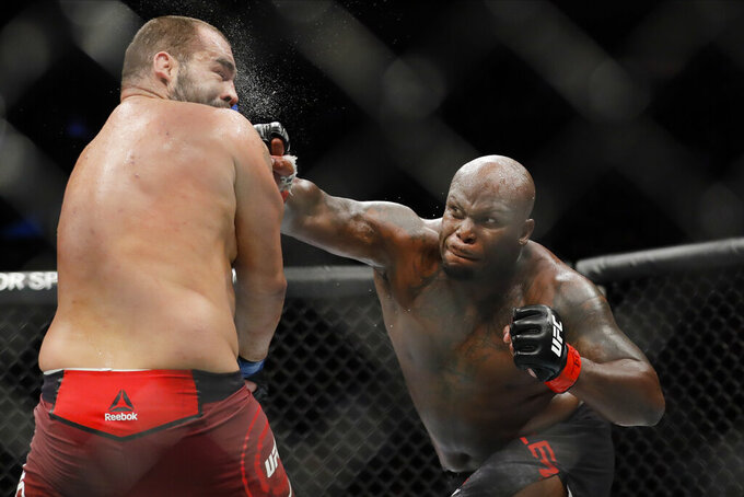 FILE - In this Nov. 2, 2019, file photo, Derrick Lewis, right, punches Bulgaria's Blagoy Ivanov during the second round of a heavyweight mixed martial arts bout at UFC 244 in New York. Lewis won the fight. Lewis is scheduled to fight for the interim UFC heavyweight title Saturday night at UFC 265. (AP Photo/Frank Franklin II, File)