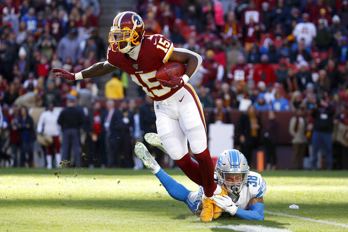 Washington Redskins' Steven Sims (15) avoids a tackle from Detroit Lions' Mike Ford (38) while returning a Lions kickoff for a touchdown during the first half of an NFL football game, Sunday, Nov. 24, 2019, in Landover, Md. (AP Photo/Alex Brandon)