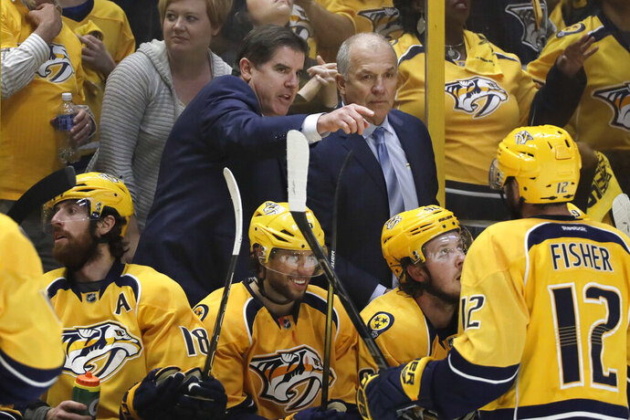 FILE - In this May 7, 2017, file photo, then-Nashville Predators coach Peter Laviolette, center left, and associated coach Kevin McCarthy, center right, talk during Game 6 of a second-round NHL hockey playoff series against the St. Louis Blues in Nashville, Tenn. Kevin McCarthy joined Peter Laviolette's Washington Capitals coaching staff as expected Wednesday, Oct. 21, 2020, continuing the pair's partnership that has lasted for more than 15 years. (AP Photo/Mark Humphrey, File)