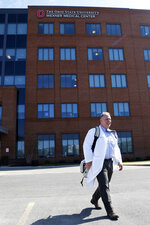 """Dr. Michael Cackovic, an OB/GYN who works at Ohio State University's Wexner Medical Center, walks through the parking lot of the Ohio State Outpatient Care facility Friday, April 23, 2021, in Upper Arlington, Ohio. When Republican lawmakers across the U.S. kept passing bans on abortion at what they term """"the first detectable fetal heartbeat,"""" he was exasperated. Yet bans pegged to the """"fetal heartbeat"""" concept have been signed into law in 12 states, including Cackovic's home state of Ohio, with another awaiting a governor's signature. (AP Photo/Jay LaPrete)"""