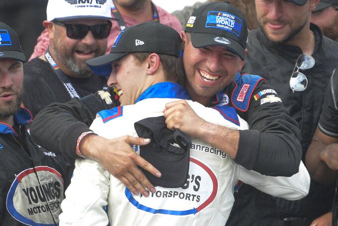 Tate Fogleman celebrates with a crew member, right, after winning the NASCAR Truck Series auto race Saturday, Oct. 2, 2021, in Talladega, Ala. (AP Photo/John Amis)