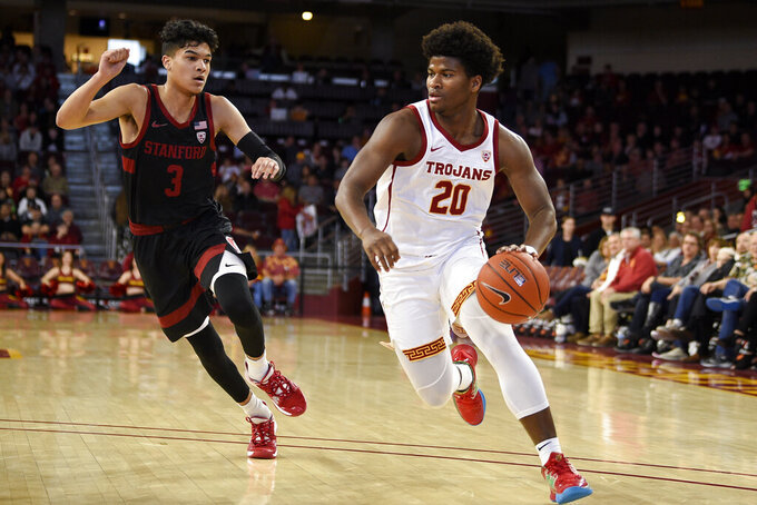 Southern California guard Ethan Anderson, right, drives to the basket past Stanford guard Tyrell Terry during the first half of an NCAA college basketball game in Los Angeles, Saturday, Jan. 18, 2020. (AP Photo/Kelvin Kuo)