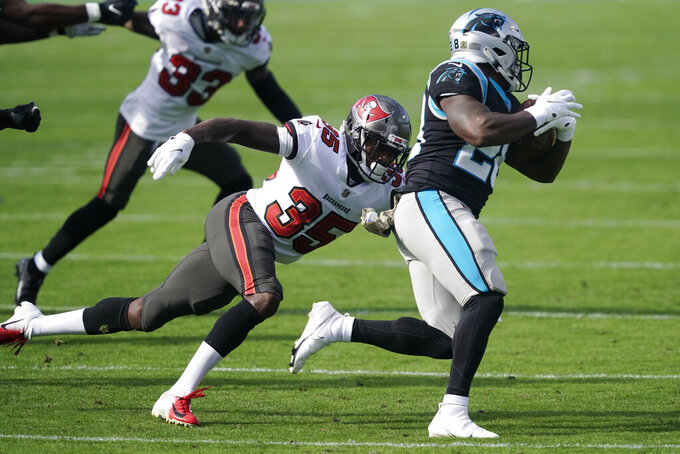 Carolina Panthers running back Mike Davis (28) runs around Tampa Bay Buccaneers cornerback Jamel Dean (35) during the first half of an NFL football game, Sunday, Nov. 15, 2020, in Charlotte , N.C. (AP Photo/Gerry Broome)