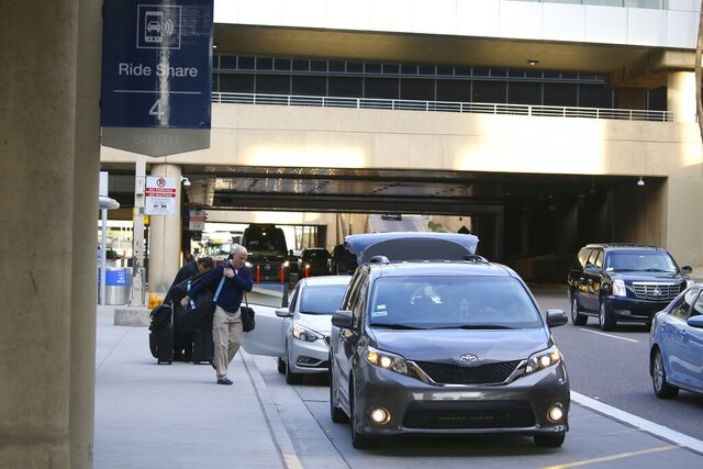FILE - In this Dec. 18, 2019, file photo passengers find their rides at the Ride Share point as they exit Phoenix Sky Harbor International Airport in Phoenix. A new $4 fee on Uber and Lyft rides to and from the Phoenix airport is