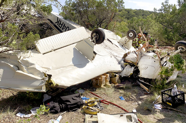 In this image provided by Austin-Travis County EMS, a single engine plane lays upside down at a wooded crash site northwest of Austin, Texas, Monday, Sept. 28, 2020. Texas Department of Public Safety Sgt. Deon Cockrell said those injured in the crash Monday were: 61-year-old Jerry Harvey; 66-year-old Barbara Harvey; and 36-year-old Jesse Kerr. Austin-Travis County EMS said all three were take to hospitals Monday. (Austin-Travis County EMS via AP)