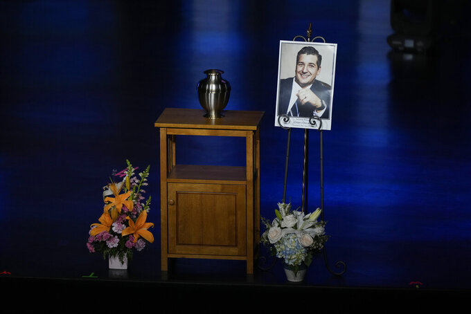 A portrait of Edgar Gonzalez, 44, who was killed last month in the Champlain Towers South condominium collapse, is displayed next to his urn during a funeral service, Friday, July 23, 2021, at Christ Fellowship church in Palmetto Bay, Fla. Gonzalez' wife Angela and daughter Deven were injured but survived the collapse, falling multiple stories.(AP Photo/Rebecca Blackwell)