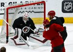 Arizona Coyotes goaltender Darcy Kuemper, left, makes a save on a shot by center Barrett Hayton (29) as defenseman Jordan Oesterle, right, applies pressure during NHL hockey practice Monday, July 13, 2020, in Glendale, Ariz. (AP Photo/Ross D. Franklin)