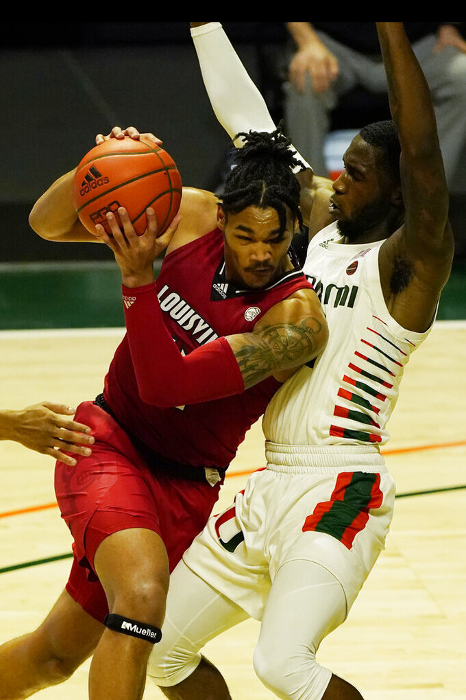 Louisville center Dre Davis (14) drives to the basket as Miami guard Elijah Olaniyi (4) defends, during the second half of an NCAA college basketball game, Saturday, Jan. 16, 2021, in Coral Gables, Fla. (AP Photo/Marta Lavandier)