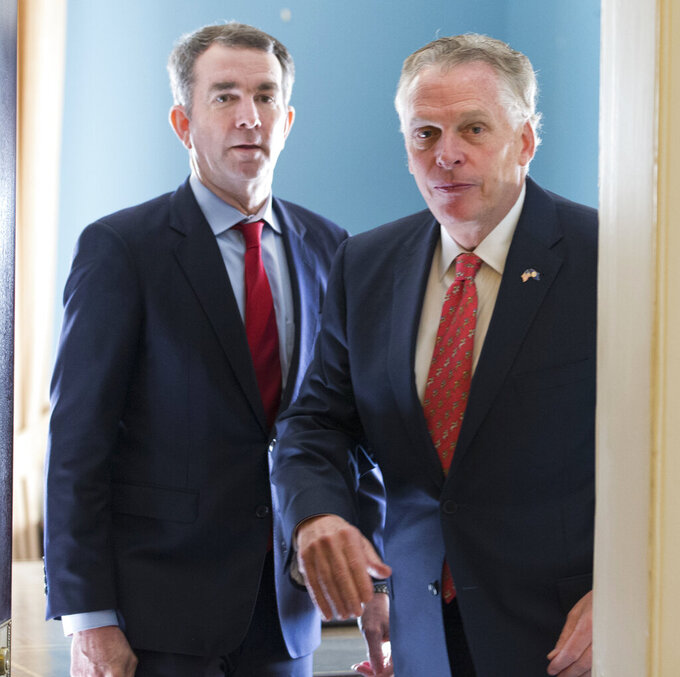 FILE - In this Jan. 9, 2018, file photo, former Virginia Gov. Terry McAuliffe, right, arrives as he and Gov. Ralph Northam, arrive for a press conference at the Capitol in Richmond, Va. Northam announced Thursday, April 8, 2021, that he was backing Terry McAuliffe in the race to succeed him, handing his predecessor one of the contest's most coveted endorsements. (AP Photo/Steve Helber, File)