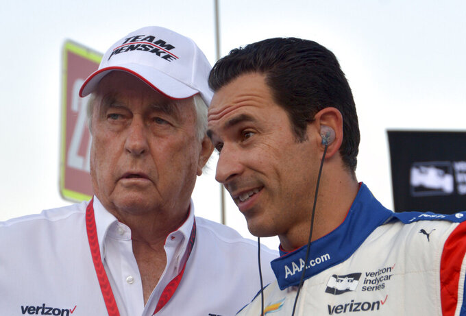 FILE - In this June 10, 2017, file photo, team owner Roger Penske, left, talks with driver Helio Castroneves, of Brazil, on pit road before an IndyCar auto race at Texas Motor Speedway in Fort Worth, Texas. Helio Castroneves is optimistic team owner Roger Penske will give him another chance to win the Indianapolis 500 for the fourth time next year. Castroneves said it will depend largely on finding a sponsor, a search he believes will be helped greatly by the fact that another Penske driver, Simon Pagenaud, won Indy in May. (AP Photo/Randy Holt, File)