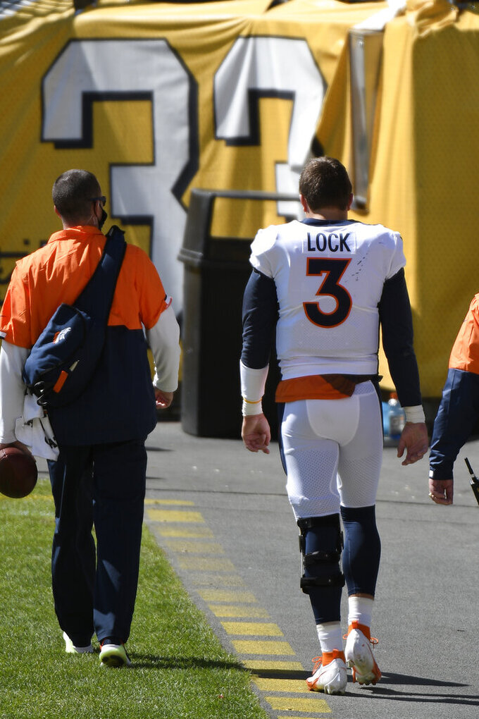 Denver Broncos quarterback Drew Lock (3) walks off the field with a team trainer after being injured during the first half of an NFL football game against the Pittsburgh Steelers in Pittsburgh, Sunday, Sept. 20, 2020. (AP Photo/Don Wright)