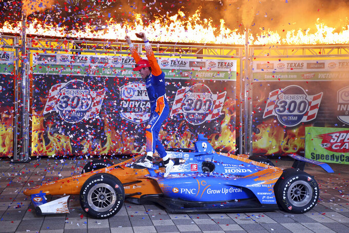 Scott Dixon jumps off his car as he celebrates winning the IndyCar Series auto race at Texas Motor Speedway on Saturday, May 1, 2021, in Fort Worth, Texas. (AP Photo/Richard W. Rodriguez)