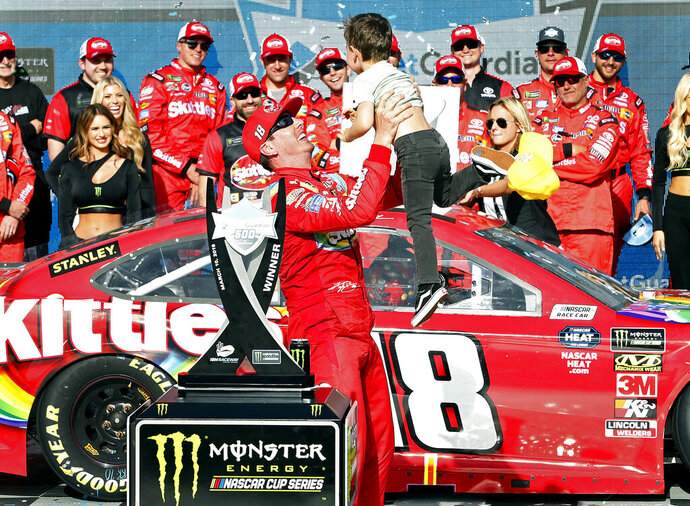 Kyle Busch tosses his son Brexton in the air after winning the NASCAR Cup Series auto race at ISM Raceway, Sunday, March 10, 2019, in Avondale, Ariz. (AP Photo/Ralph Freso)
