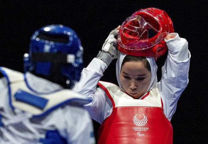Zakia Khudadadi of Afghanistan (red) removes her helmet during her bout with Ziyodakhon Isakova of Uzbekistan (blue) in the women's K44 49kg round of 16 taekwondo at the Tokyo 2020 Paralympic Games in Chiba, near Tokyo Thursday, Sept. 2, 2021. (Joe Toth for OIS via AP)