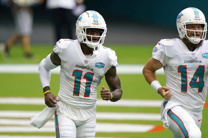 Miami Dolphins wide receiver DeVante Parker (11) and quarterback Ryan Fitzpatrick (14) return to the bench after Parker scored a touchdown, during the first half of an NFL football game against the Buffalo Bills, Sunday, Sept. 20, 2020 in Miami Gardens, Fla. (AP Photo/Wilfredo Lee)