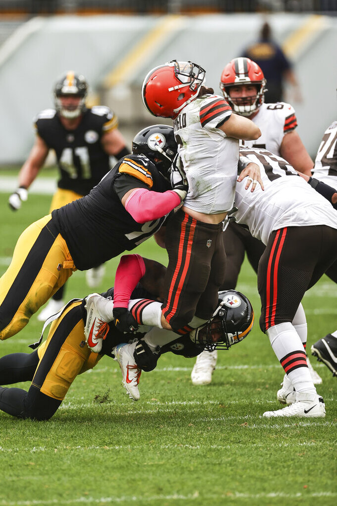 Cleveland Browns quarterback Baker Mayfield (6) is wedged during a sack by Pittsburgh Steelers defensive end Stephon Tuitt (91) in an NFL game, Sunday, Oct. 18, 2020, in Pittsburgh. The Steelers defeated the Browns 38-7. (Margaret Bowles via AP)