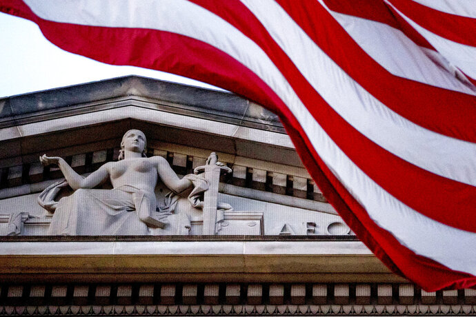 FILE - In this March 22, 2019 file photo, an American flag flies outside the Department of Justice in Washington.  (AP Photo/Andrew Harnik)
