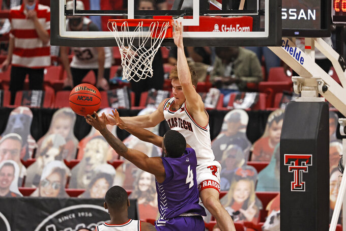Texas Tech's Mac McClung, top, fouls Abilene Christian's Damien Daniels (4) while blocking a shot during the second half of an NCAA college basketball game Wednesday, Dec. 9, 2020, in Lubbock, Texas. (AP Photo/Brad Tollefson)