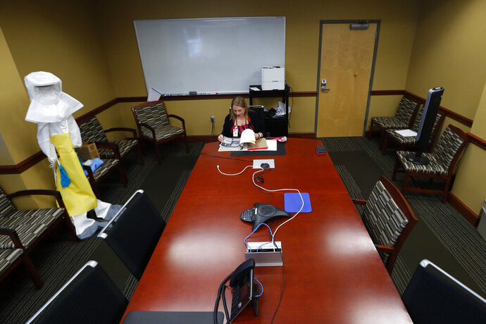 Jennifer Gottschalk, environmental health supervisor of the Toledo-Lucas County Health Department, works in an empty conference room in Toledo, Ohio, on Wednesday, June 24, 2020. At least 38,000 state and local public health jobs nationwide have disappeared since the 2008 recession, leaving a skeletal workforce for what was once viewed as one of the world's top public health systems. (AP Photo/Paul Sancya)