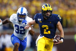 Michigan quarterback Shea Patterson (2) runs past Middle Tennessee linebacker Chris Melton (32) in the first half of an NCAA college football game in Ann Arbor, Mich., Saturday, Aug. 31, 2019. (AP Photo/Paul Sancya)