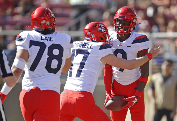Arizona's Jalen Johnson, right, is congratulated by quarterback Grant Gunnell (17) and Donovan Laie (78) after scoring a touchdown against Stanford during the first half of an NCAA college football game Saturday, Oct. 26, 2019, in Stanford, Calif. (AP Photo/Ben Margot)