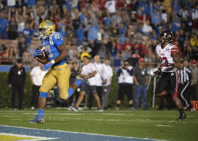 UCLA running back Joshua Kelley, left, sprints for a touchdown past Utah defensive back Julian Blackmon during the first half of an NCAA college football game Friday, Oct. 26, 2018, in Pasadena, Calif. (AP Photo/Kyusung Gong)