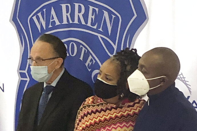 Warren, Mich., Mayor James Fouts, left, stands with Candace and Eddie Hall during a news conference, Wednesday, Sept. 30, 2020, at police headquarters in Warren. A 24-year-old white man has been charged with ethnic intimidation and other counts for firing shots into the Hall's home just north of Detroit after the family put a Black Lives Matter sign in their front window. (AP Photo/Corey Williams)