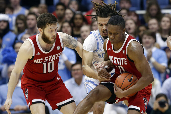 North Carolina guard Cole Anthony, center, reaches for the ball between North Carolina State guard Braxton Beverly (10) and guard C.J. Bryce during the first half of an NCAA college basketball game in Chapel Hill, N.C., Tuesday, Feb. 25, 2020. (AP Photo/Gerry Broome)