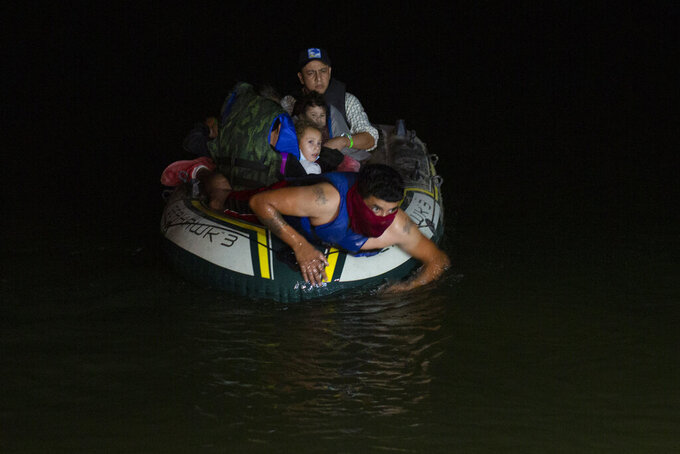 FILE - In this March 30, 2021 file photo, a smuggler takes migrants, mostly from Central American countries, on a small inflatable raft towards U.S. soil, in Roma, Texas. Mexico President Andres Manuel Lopez Obrador said Wednesday, April 14, 2021, it was protecting human rights that was motivating Mexico's efforts to stop child migrants en route to the U.S. from being smuggled into the country. (AP Photo/Dario Lopez-Mills, File)
