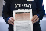 In this Monday, Dec. 16, 2019, photo, a booklet is held up during an exercise run by military and national security officials, for state and local election officials to simulate different scenarios for the 2020 elections, in Springfield, Va. These government officials are on the front lines of a different kind of high-stakes battlefield, one in which they are helping to defend American democracy by ensuring free and fair elections. (AP Photo/Alex Brandon)