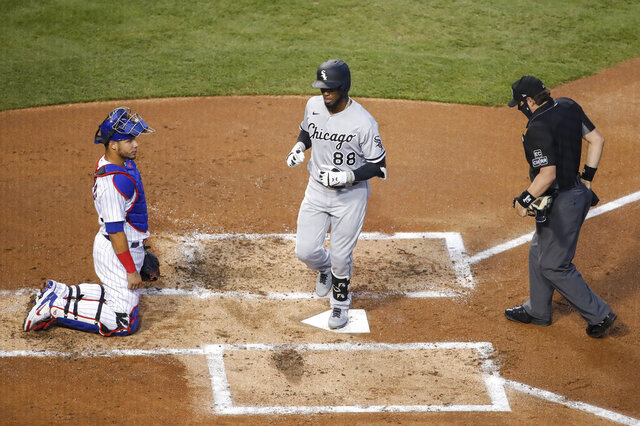 CORRECTS TO TWO-RUN HOME RUN NOT A SOLO HOME RUN - Chicago White Sox's Luis Robert, center, crosses home plate after hitting a two-run home run off of Chicago Cubs starting pitcher Jon Lester, as catcher Willson Contreras, left, looks on, during the second inning of a baseball game, Friday, Aug. 21, 2020, in Chicago. (AP Photo/Kamil Krzaczynski)